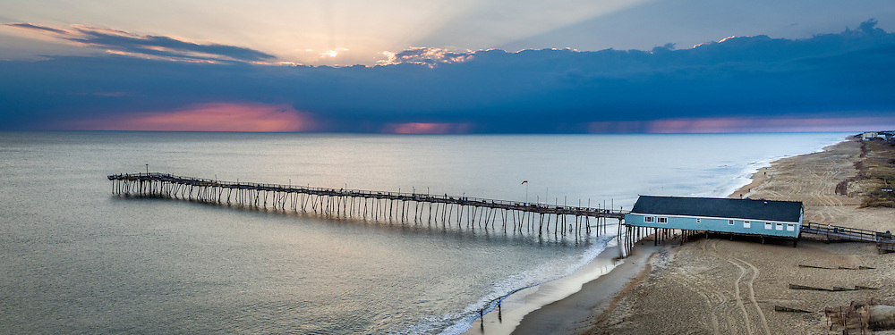 Sun rises over storm at Avalon Fishing Pier on the Outer Banks, NC.