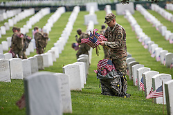 May 23, 2019 - Arlington, VA, United States of America - Soldiers with the 3d U.S. Infantry Regiment place flags at headstones during Flags-in at Arlington National Cemetery marking the start of the Memorial Day holiday May 23, 2019 in Arlington, Virginia. (Credit Image: © Nicholas T. Holmes via ZUMA Wire)