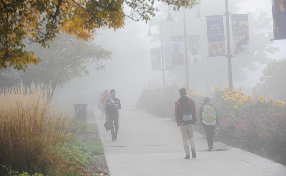 Students make their way to class through a blanket of fog on an early fall morning.