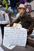 A man with a sign suggesting that Obama should fund retirement homes with job plan funds.