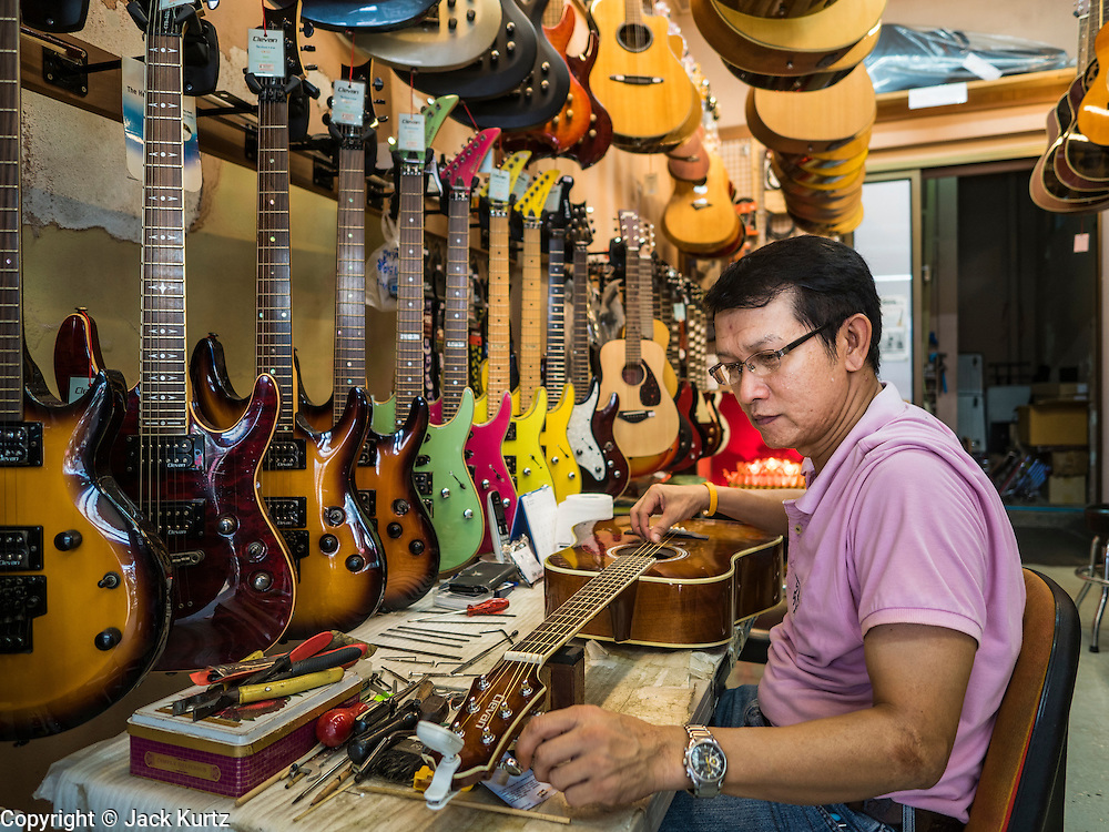 22 MARCH 2016 - BANGKOK, THAILAND: A worker restrings a guitar in an instrument shop in Verng Nakorn Kasem. Verng Nakorn Kasem, also known as the Thieves' Market, was one of Bangkok's most famous shopping districts. It is located on the north edge of Bangkok's Chinatown district, it grew into Bangkok's district for buying and selling musical instruments. The family that owned the land recently sold it and the new owners want to redevelop the famous area and turn it into a shopping mall. The new owners have started evicting existing lease holders and many of the shops have closed. The remaining shops expect to be evicted by the end of 2016.          PHOTO BY JACK KURTZ