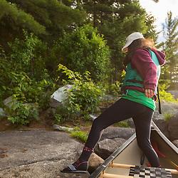 A teenage girl exits a canoe on Bald Mountain Pond. Bald Mountain Township, Maine.