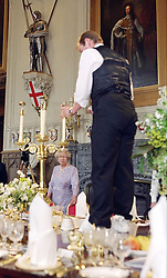 Preparations for the State Banquet in St Georges Hall, Windsor Castle. .Photo by Ian Jones..HM The Queen inspects the banquet table as Stephen Marshall, Yeoman of the glass and china pantry adjusts the table settings..
