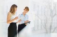 Smiling businesswomen with tablet PC and folder working by railing in office