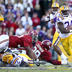 November 6, 2010; Baton Rouge, LA, USA; LSU Tigers running back Stevan Ridley (34) breaks away from Alabama Crimson Tide linebacker Dont'a Hightower (30) and defensive tackle Josh Chapman (99) during the second half at Tiger Stadium. LSU defeated Alabama 24-21.  Mandatory Credit: Derick E. Hingle