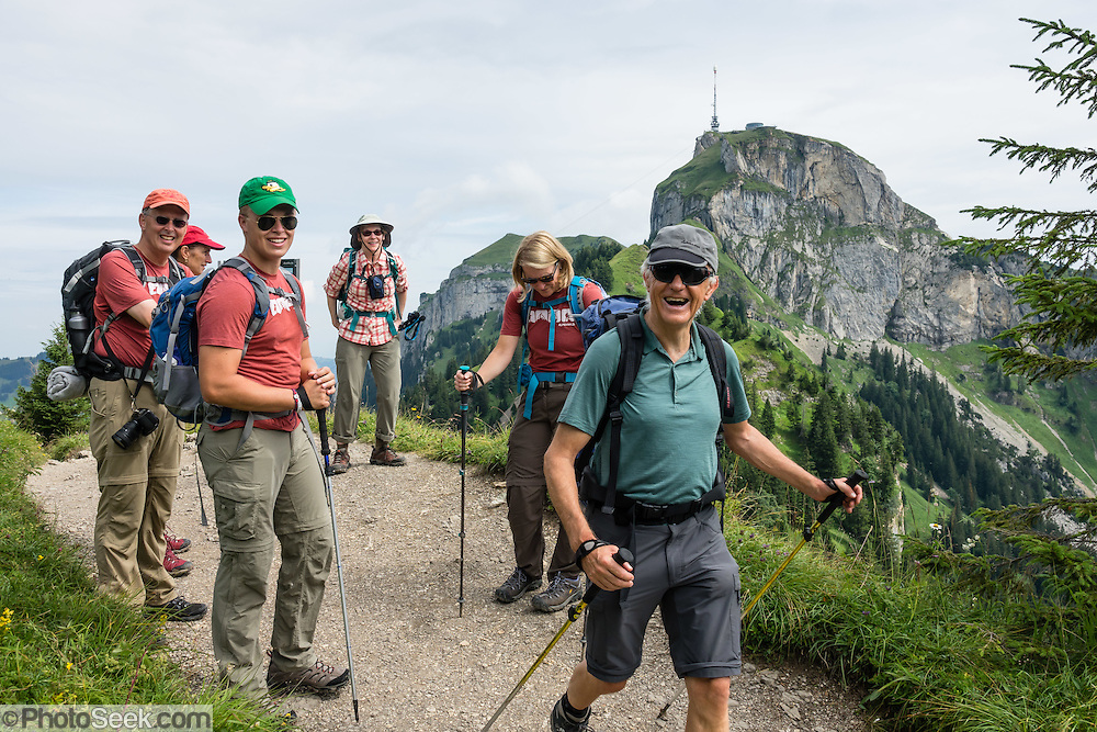 Hikers traverse a ridge of Hoher Kasten mountain in the Alpstein limestone range, Appenzell Alps, Switzerland. Hoher Kasten (1795 m) is on the border between the cantons of Appenzell Innerrhoden and St. Gallen. Appenzell Innerrhoden is Switzerland's most traditional and smallest-population canton (second smallest by area). For licensing options, please inquire.
