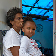 Punta Santiago, PR--Hilda Alicea Gonz'lez, left, sits with her granddaughter, Hidachis Antongiorge Torres, on the front porch of her home in Punta Santiago, PR, November 8, 2017. Ms. Gonz'lez received a blue tarp a week earlier, which replaces her roof  which blew off during Hurricane Maria. September 20, 2017. Nearly two months after the storrm, her home has no running water or electricity. The storm brought a surge of water that filled her home with 3 feet of water. Her home continues to be surrounded by stagnant water due to poor drainage and continued rain. Photo by Lori Waselchuk/BRAF
