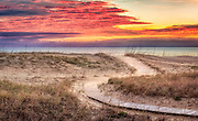 Clouds at sunris with a curvy path leading to a Kitty Hawk Beach on the Outer Banks of NC.