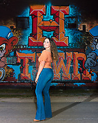 Graduation portrait of senior girl in front of H-Town mural in EADO district of Houston, Texas.