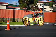 a road worker uses a road roller compactor to compact the new road surface at Browns Bay, Auckland, New Zealand