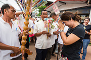 29 JUNE 2014 - DAN SAI, LOEI, THAILAND:  A woman donates money to a group of people in a merit making procession walk through Dan Sai on the their way to Wat Ponchai on the last day of the Ghost Festival. Phi Ta Khon (also spelled Pee Ta Khon) is the Ghost Festival. Over three days, the town's residents invite protection from Phra U-pakut, the spirit that lives in the Mun River, which runs through Dan Sai. People in the town and surrounding villages wear costumes made of patchwork and ornate masks and are thought be ghosts who were awoken from the dead when Vessantra Jataka (one of the Buddhas) came out of the forest. On the last day of the festival people participate in merit making ceremonies at the Wat Ponchai in Dan Sai and lead processions through town soliciting donations for the temple.   PHOTO BY JACK KURTZ