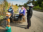 24 JANUARY 2017 - PHRA THAEN, KANCHANABURI, THAILAND:  Sugarcane workers take a break on the side of a rural highway in Phra Thaen. Thai government  officials recently announced that they plan to float sugar prices later this year or early in 2018. Wholesale prices are currently set by the Cane and Sugar Board, a part of the Industry Ministry, while the Commerce Ministry sets the retail price. Thailand has fixed retail prices of sugar to guarantee a profit for farmers. Thailand is the world's leading exporter of sugar, after Brazil. Thai sugar production is expected to drop by more than three percent because of the lingering drought that crippled agriculture through 2015 and 2016.   PHOTO BY JACK KURTZ