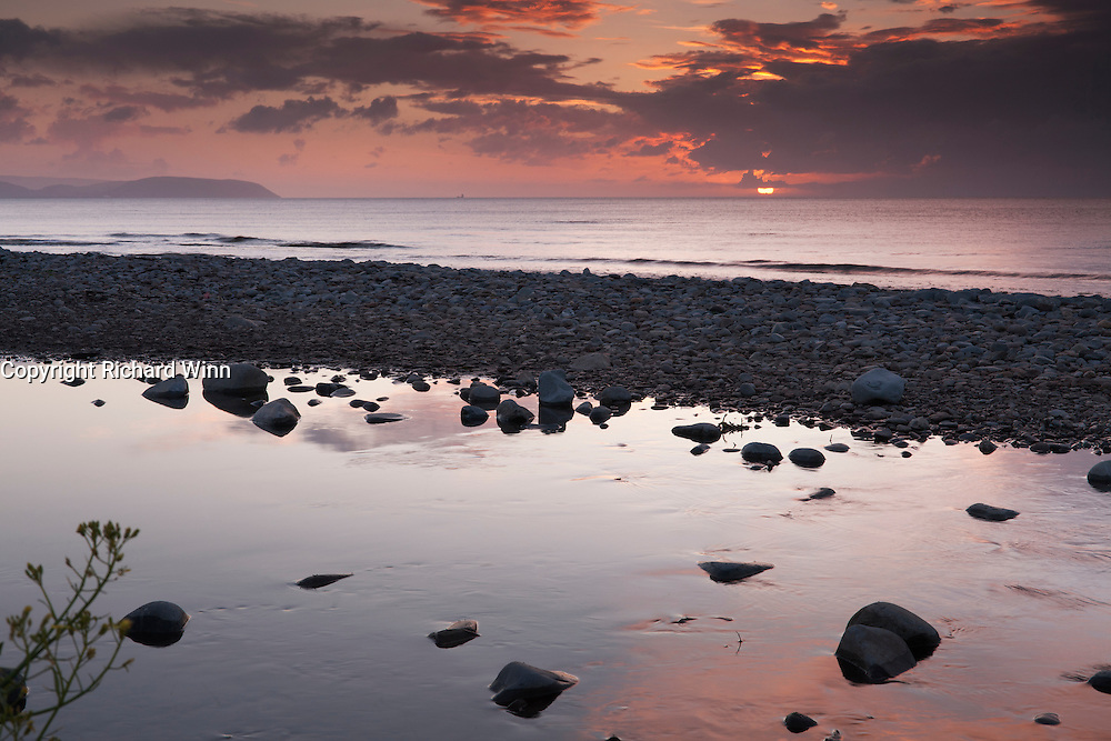 Sunset over Bristol Channel, with reflections of the red sky in the pool at Kilve Pill, the outflow of the River Holford at Kilve Beach.