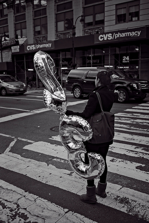 Woman with balloons hailing taxi, New York, NY, US