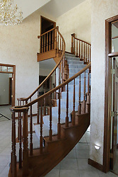 A solid oak curving staircase stretches between floors in a modern home and is carpeted in the middle for traction, wear, safety and looks.