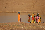 Desert village women and girls fetching water in the Thar desert near Jaisalmer, Rajasthan, India. The Thar desert borders Pakistan and the Sam Sand Dunes is a popular tourist attraction..Photo by Suzanne Lee