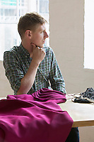 Tailor sitting at sewing table looking at window