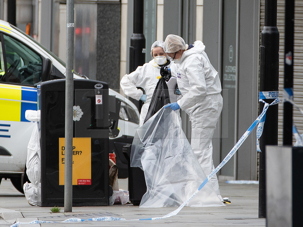 © Licensed to London News Pictures. 11/10/2019. Manchester, UK. Forensic scenes of crime examiners remove the contents of a bin at the foot of steps to the Arndale Centre on Exchange Square . Terrorism Police are investigating after four people were stabbed during a single attack at the Arndale Centre in Manchester City Centre . Photo credit: Joel Goodman/LNP