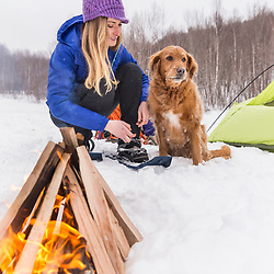 A woman and her dog sit next to a campfire while winter camping in New Hampshire's White Mountains.