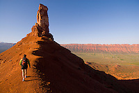 A young woman hikes along a ridgeline trail in Castle Valley near Moab, Utah.
