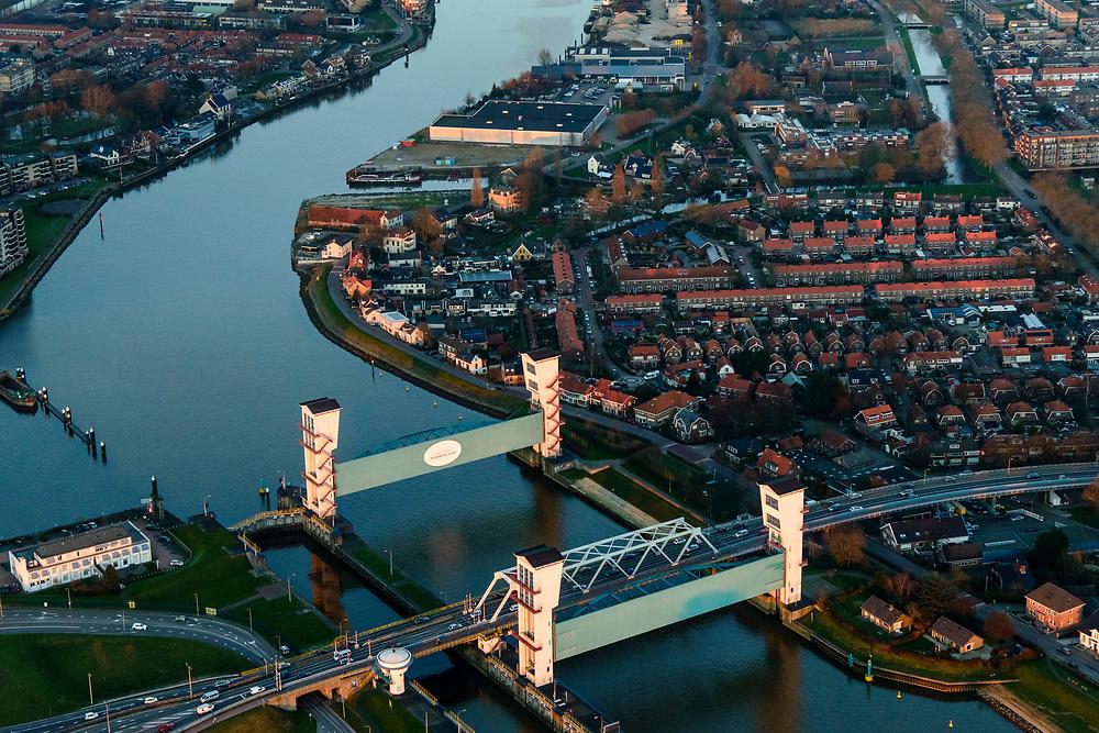 Nederland, Zuid-Holland, Krimpen aan de IJssel, 07-02-2018; stormvloedkering in de Hollandsche IJssel in de avondschemering. Bij storm en dreigend hoog water wordt een van de twee schuiven naar beneden gelaten, de tweede schuif dient al reserve. De scheepvaart kan de gesloten kering paseren via de naastgelegen schutsluis. De stormvloedkering maakt deel uit van de Deltawerken en is als eerste voltooid in 1958. <br /> Krimpen at the river IJssel, near Rotterdam: storm surge barrier, protects the highly populated western part of Holland, which lies below sea level. In case of storm and threat of high water, one of the two doors is lowered into the river (the second door is a spare one). The lock next to the barrier allows shipping when the barrier is closed.<br /> luchtfoto (toeslag op standard tarieven);<br /> aerial photo (additional fee required);<br /> copyright foto/photo Siebe Swart