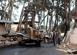 © under license to London News Pictures. 23/02/2011. Men watch as a forklift carries the remains of burnt out cars at the Army Depot near Lubrique, Libya. Fighting there between forces loyal to Gadaffi and the Opposition lasted for three days.  Photo credit should read Michael Graae/London News Pictures
