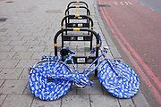 A ladies bike covered in blue plastic wrapping tape is locked up on an empty bike stand in south London.