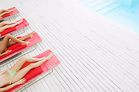 Young Women Sunbathing by pool on deckchairs low section high angle view