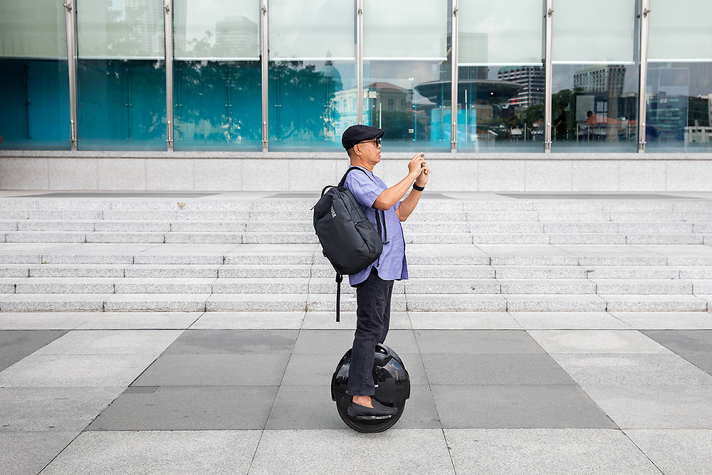 A man uses his smart phone while riding a personalised motorised device at Boat Quay, Singapore.