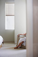 Woman sitting on armchair in bedroom low section