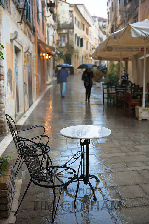 Deserted cafe table and chairs in rainy day scene in Kerkyra, Corfu Town, Greece