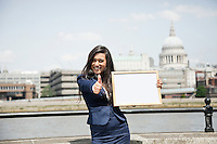 Indian businesswoman gesturing thumbs up as she holds Moodboard sign with St. Paul's Cathedral in background