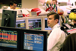 Stock photo of a man working at at a station with several monitors and a telephone line