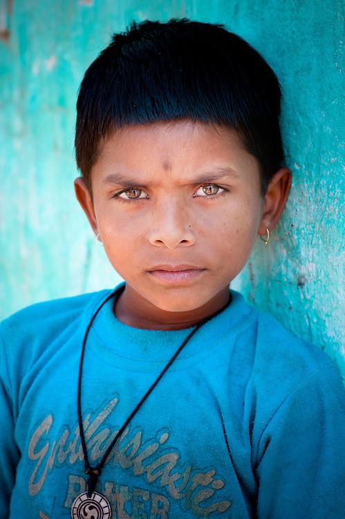 Young Rajasthani boy leaning against blue wall, Thar desert, India.