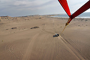 Angola, Namibe Province, Iona National Park. Flamingo lodge Fishing camp in the desert on the Atlantic coast. Parasailing on beach with a parachute tide to the back on a 4x4 vehicle.<br /> <br /> Photo: &copy; Zute &amp; Demelza Lightfoot