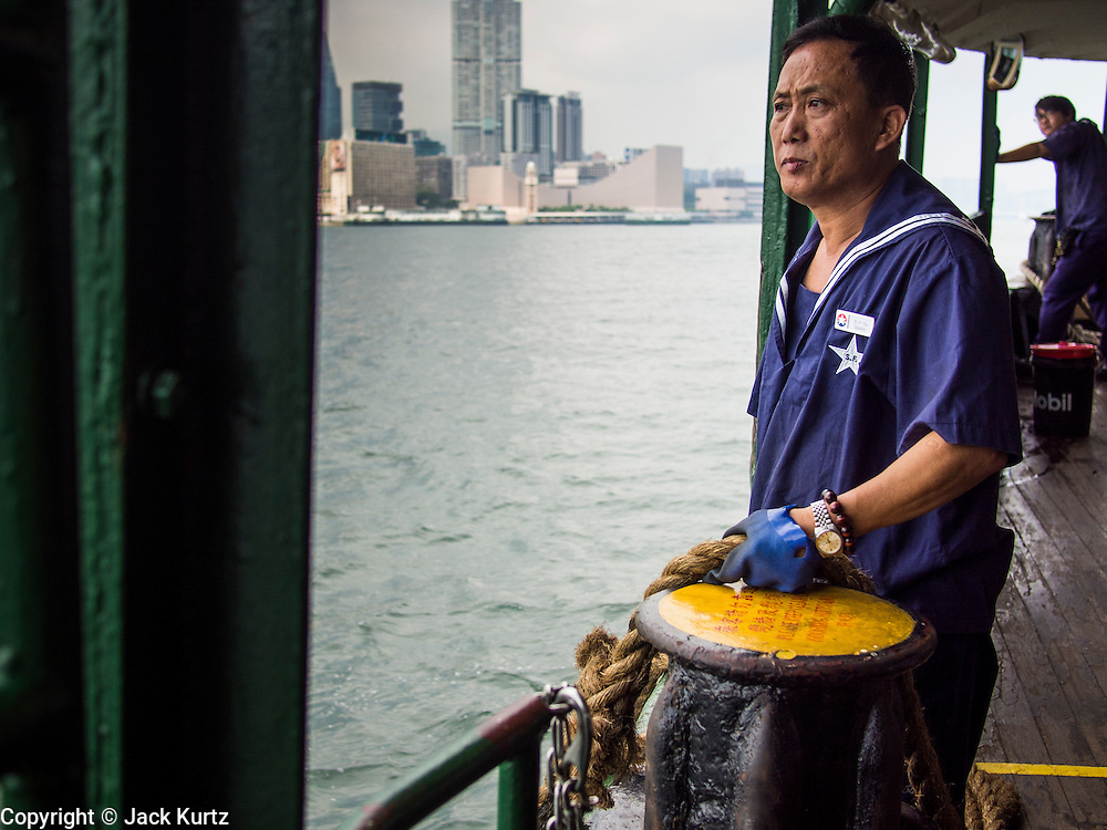 "10 AUGUST 2013 - HONG KONG:  A Star Ferry worker looks at the shore on the Hong Kong side of Victoria Harbor (Kowloon is in the background). The Star Ferry, or The ""Star"" Ferry Company, is a passenger ferry service operator and tourist attraction in Hong Kong. Its principal routes carry passengers across Victoria Harbour, between Hong Kong Island and Kowloon. It was founded in 1888 as the Kowloon Ferry Company, adopting its present name in 1898.<br /> The fleet of twelve ferries currently operates two routes (four prior to April 1, 2011) across the harbour, carrying over 70,000 passengers a day, or 26 million a year. Even though the harbour is crossed by railway and road tunnels, the Star Ferry continues to provide an inexpensive mode of harbour crossing. The company's main route runs between Central and Tsim Sha Tsui. Hong Kong is one of the two Special Administrative Regions of the People's Republic of China, Macau is the other. It is situated on China's south coast and, enclosed by the Pearl River Delta and South China Sea, it is known for its skyline and deep natural harbour. Hong Kong is one of the most densely populated areas in the world, the  population is 93.6% ethnic Chinese and 6.4% from other groups. The Han Chinese majority originate mainly from the cities of Guangzhou and Taishan in the neighbouring Guangdong province.      PHOTO BY JACK KURTZ"