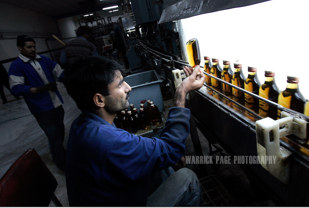 A quality control inspector checks a bottle of whiskey on the production line at the Murree Brewery, Wednesday, February 14, in Rawalpindi, Pakistan.  The brewery boasts the first 20 year-old malt whiskey in the Muslim world, due for release in mid-2007. Established more than a century ago under British Raj, Murree Brewery also is Pakistan's oldest company and one of two breweries in a country under prohibition. Muslims have been banned from drinking alcohol since it was outlawed in 1977, but Christians and Hindus may still buy alcohol. The brewery hopes to export the exclusive whiskey to Europe and the Middle East. (Photo by Warrick Page)