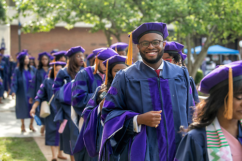 Howard students in graduation regalia walking in line.