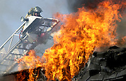 Photo by Gary Cosby Jr.  Decatur firefighter Joe Webb directs water on a burning apartment building in Hartselle, Al., as the blazes destroys the building.  The people died in the fire after being trapped in an upstairs bedroom.