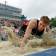 Carroll's Adam Haluska splashes into the long jump pit winning the event in 3A at the Boy's State Track Meet.  photo by David Peterson