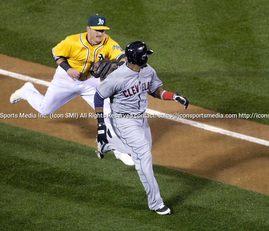 March 31, 2014 - Oakland, CA, USA - Oakland Athletics third baseman Josh Donaldson tags out Cleveland Indians' Carlos Santana, who was caught between third and home on a comebacker to the pitcher during the fourth inning of their season-opening Major League Baseball game, Monday, March 31, 2014 at O.co Coliseum in Oakland, Calif