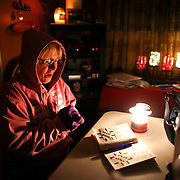 Doris Woodward warms her hands as she takes a break from a cross-word puzzle on Friday, January 20, 2012 in Auburn, Wash. Power was out in her home and she was without heat. An ice storm wreaked havoc in the area, bringing down trees and power lines. Power was out in large parts of the area. (AP Photo/seattlepi.com, Joshua Trujillo)