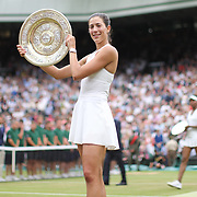 LONDON, ENGLAND - JULY 15:  Garbine Muguruza of Spain with the winners trophy after victory in the Ladies Singles final as Venus Williams of The United States walks back to her seat with the runners up trophy during the Wimbledon Lawn Tennis Championships at the All England Lawn Tennis and Croquet Club at Wimbledon on July 15, 2017 in London, England. (Photo by Tim Clayton/Corbis via Getty Images)