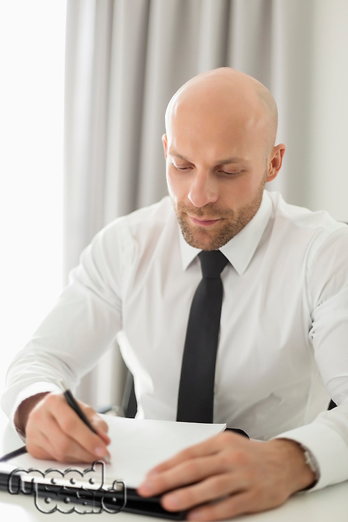 Mid adult businessman writing on clipboard in home office