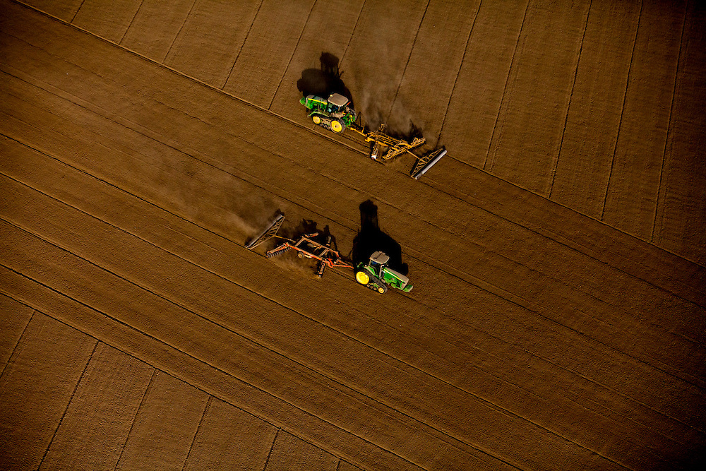 Tractors till a field to prepare it for strawberry farming in Ventura County, California, U.S. on Wednesday May 21, 2014.