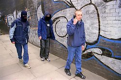 Teenage young offenders approaching pedestrian in preparation for stealing mobile phone,