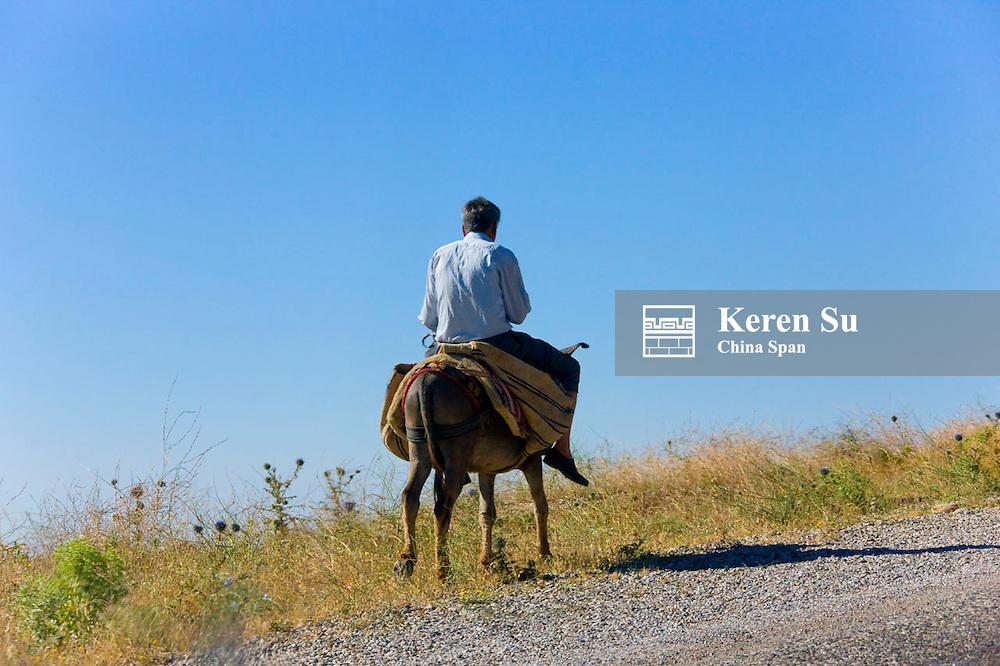 Riding on donkey in the village, Kocahisar, Turkey
