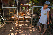 EVA RUPPEL stands in front of one of many gated pens separating 170 rescued street dogs on her rural property near Kandy, Sri Lanka, on Wednesday, February 21, 2018. Ruppel does not cage the animals, allowing them freedom to interact in small packs. Ruppel created Tikiri Trust, with the financial assistance of her father, to rescue and rehome Sri Lanka's street dogs.<br /> <br /> It is impossible to visit Sri Lanka without seeing street dogs in nearly every public space, near hotels, guest houses and restaurants, schools, offices, markets, hospitals, police stations, bus terminals, railway stations, temples, etc. These dogs do not have their own homes, but they are usually highly tolerated and are typically fed collectively by people in a particular area.<br /> <br /> According to the NGO, Kandy Association for Community Protection through Animal Welfare (KACPAW), 100 unsterilized dogs will give rise to 3,000 dogs in one year. The Sri Lankan government, as well as several NGOs, work to spay/neuter animals, but there is need to educate the public and maintain funds to stay on top of their efforts.<br /> <br /> Eva Ruppel left Germany for a three-month visit to Sri Lanka, which included time in a Buddhist meditation retreat, and she remains in this island nation 37 years later.<br /> <br /> While married, Ruppel&rsquo;s husband asked that the couple keep only three dogs in their home at any one time, and she respected his wishes. This 60-something year old lost her husband to a ruptured brain blood vessel in 1995 when he was 51 years old, after nine years of marriage. After his death, she began rescuing more and more animals and she now lives with 170 dogs, plus a dozen or so cats.<br /> <br /> With the support of her father, she started Tikiri Trust. Her father passed away in 2011, and he left her an inheritance, which she continues to use to support her cause. <br /> <br /> Ruppel, who is fluent in German, English and Sinhala, said that she has found homes for &ldquo;hundreds, if not thousands&rdquo; of dogs. She also provides free spay/neuter clin