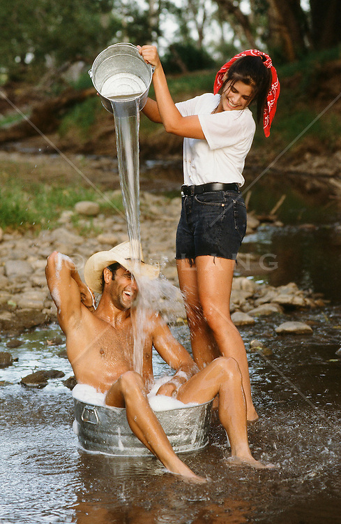 woman pouring water from a bucket over a cowboy's head in a bucket