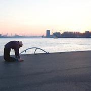 Nederland Rotterdam 21-03-2009 20090321Foto: David Rozing ..Rotterdam kop van zuid, vrouw doet verschillende oefeningen, een mix van joga, dans, capoeira, martial fighting art en meditatie. lenig, lenige, rekken,   Woman doing physical exercise in open air in city of Rotterdam   Foto: David Rozing